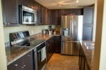 Fully stocked kitchen to prepare a culinary feast with stainless steel appliances and granite countertops.