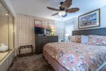 master bedroom suite,king bed, dresser, television, palm leaf style ceiling fan, jacuzzi hot tub, luggage rack