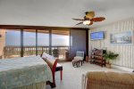 Master bedroom ocean views from a king bed and sitting chairs