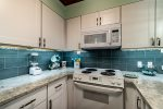 white kitchen cabinets, white microwave, white oven-range, blue tile back splash, granite counter tops