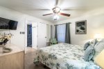 master suite king size bed, television, ceiling fan with light, shower, wall art, beach decor