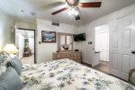master suite king size bed, television, privacy door, shower, dresser, wall art, beach decor