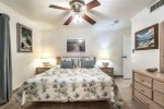 master suite king size bed, dresser, ceiling fan with light, shower, wall art, beach decor