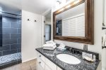 granite counter vanity, mirror, extra large shower with two shower heads, brick layed tile work