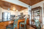 breakfast bar, bar stools, decor display, pendant light, kitchen cabinets, stainless appliances