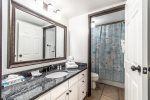 guest bathroom vanity and mirror, granite counter tops, white cabinets, tub and shower, toilet