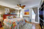 master suite with king size bed, custom barn door entry, beach art, palm leaf ceiling fan