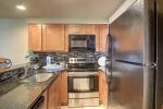 Galley kitchen with full size appliances, custom cabinets, and granite counters