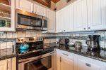 kitchen with granite counter tops, stainless appliances, kitchen amenities, upgraded cabinets