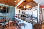 breakfast bar, bar stools, dining table, television, stainless steel appliances, saltillo tile, wood ceiling, television