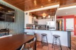breakfast bar, bar stools, dining table, television, stainless steel appliances, saltillo tile, wood ceiling