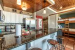 kitchen area, breakfast bar, bar stools, granit counter tops, updated cabinets, stainless refrigerator