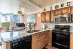 updated kitchen cabinets, granite counter tops, microwave, range-oven, dishwasher, coastal wall art