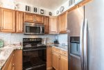 kitchen with upgraded cabinets, stainless steel microwave and refrigerator, oven-range, blender, beach art