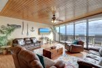 living room area, bay windows, gulf views, ceiling fan, sofa, recliner, wood floors, wood ceiling
