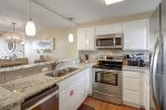 kitchen with stainless steel appliances, upgraded kitchen cabinets, granite counters, tile back splash, pendant lights