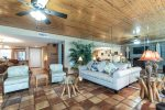 living area with beach decor, sitting chairs, sofa, saltillo tile, wood ceiling, wall mirrors