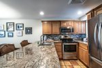 kitchen with granite counters, stainless steel appliances, decorative tile back splash