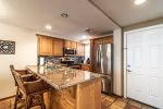 kitchen with breakfast bar with granite counters, stainless steel appliances, decorative tile back splash