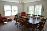 The bright dining room, large table with seating for 8. There is also additional seating at the kitchen counter.