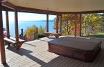 Large hot tub under main deck with lake views.