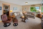 Lower level family room with large smart TV and waterfront views.
