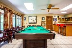 Pool table is facing a row of windows that looks out onto the screened in porch.