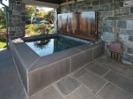 The stone hot tub with wooden cover and ocean views.