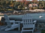Adirondack chairs looking at the sprawling ocean views in front of the home.