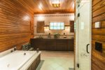 Large bathroom with a soaking tub next door to the master bedroom on the first floor.