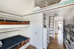 Bunk room on the second floor with four twin beds and a sleep loft with a full bed.