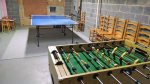 Bottom Level: Game room with ping-pong and foosball tables
