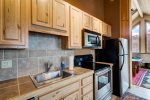 Upper level kitchenette with full oven, stove, refrigerator and dishwasher