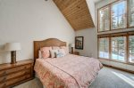 The main floor master bedroom feels light and airy with the high ceilings and large windows
