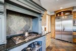The kitchen boasts a large gas range, warming drawers, a double oven and two dishwashers