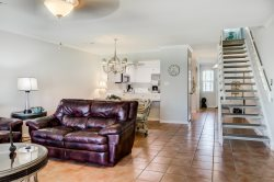 This tropical and light three-bedroom unit spans two stories and includes a rear patio overlooking the pools with a porch swing.